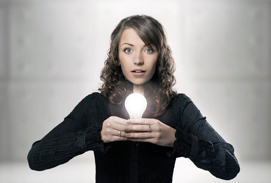 Pretty girl in black holding a glowing light bulb