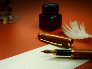 old fashioned fountain pen with blank writing paper, feather and ink quiill