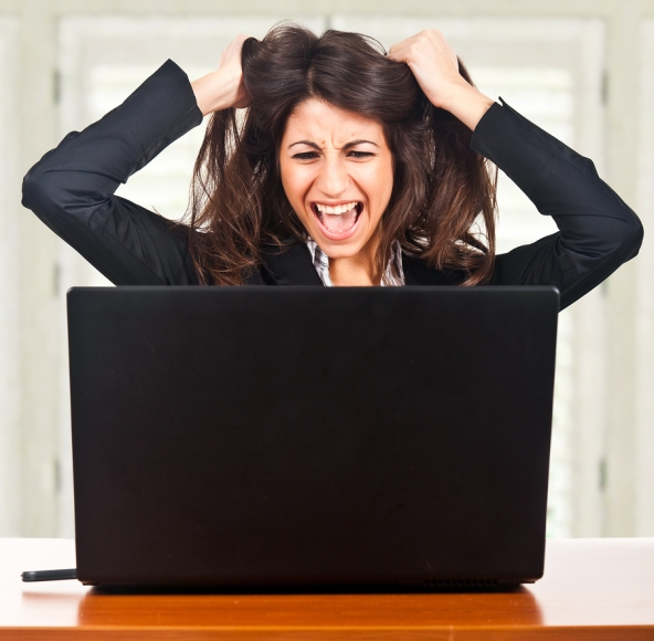 woman in front of laptop is yanking hair on both sides of her head and yelling