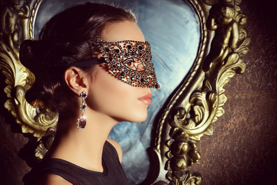Close-up portrait of a beautiful woman in venetian mask. Carnival, masquerade. Jewellery, gems.