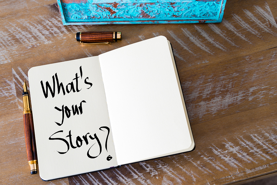 Handwritten text What's Your Story ? in notebook with fountain pen beside notebook
