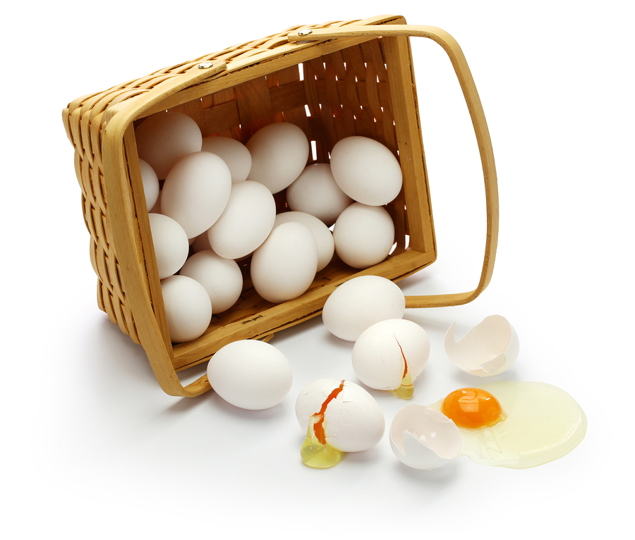 Basket of eggs on side with several outside of basket, broken open