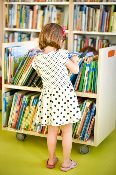 Little girl in polka dot dress has back to camera. Is choosing a book in the library to take home