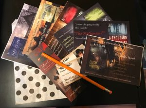 book swag for author Mae Clair includes colorful postcards, bookmark and business cards