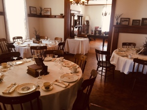 Setting for Te and Stories with Mae Clair, linen covered circular tables in old historic home with china place settings