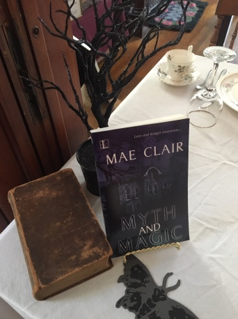 Close up of book Myth and Magic by Mae Clair in center of table set for fancy tea lunch