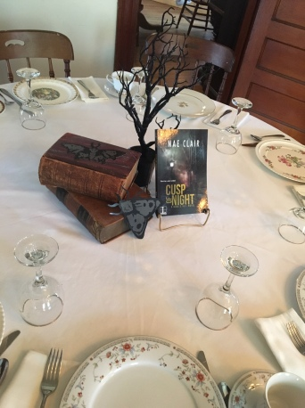 Close up of book Cusp of Night by Mae Clair in center of table set for fancy tea lunch