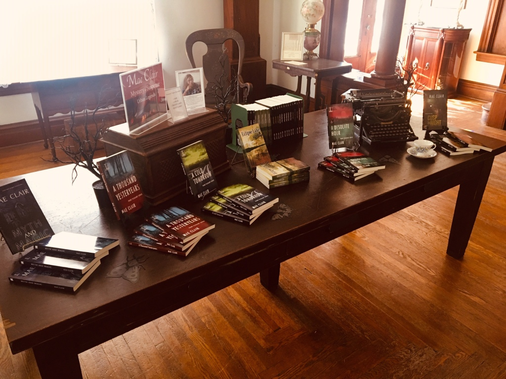 Long table with a display of books by author Mae Clair