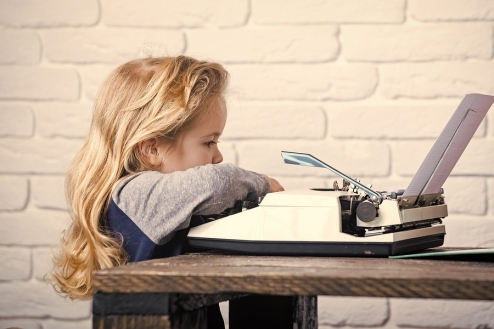 Toddler age girl with long blonde hair at a typewriter