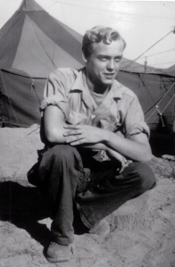 Blond haired solider in fatigues kneeling in front of an army tent in an arid setting, year 1945