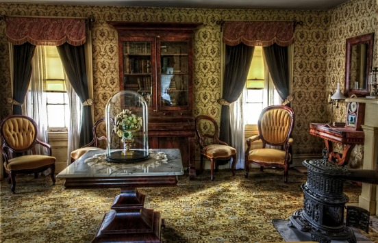 Victorian parlor with ornate furnishings, wallpaper, and two windows