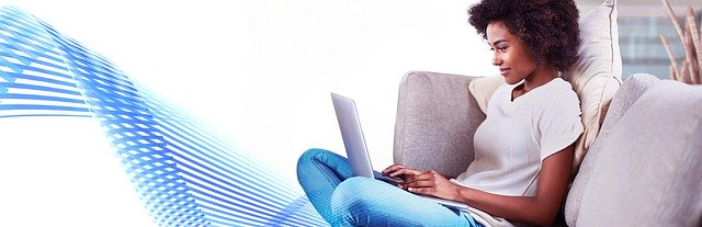 young African American woman sitting cross-legged on couch, typing on an open laptop