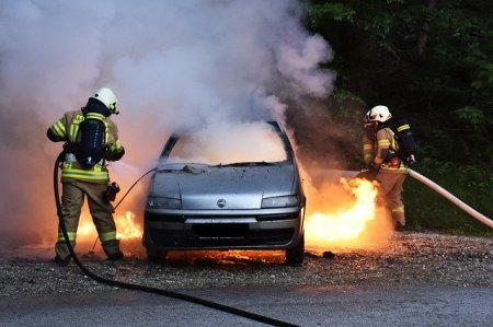 two fireman with hoses extinguishes burning flames around a smoking car