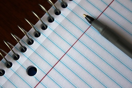 closeup of lined notebook with pen on top