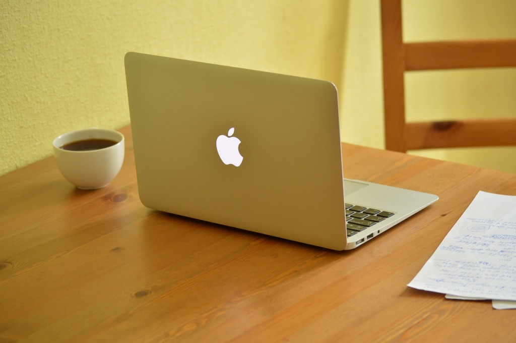 An open Macbook on a table with a cup of coffee and writing paper