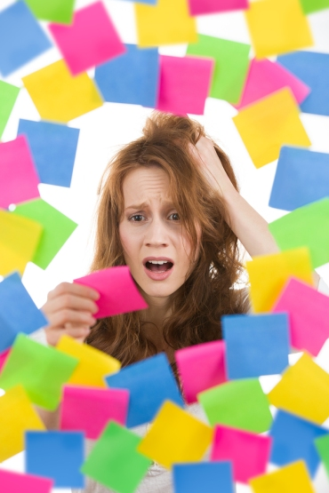 Stressed woman with pink post it note surrounded by scores of others in different colors