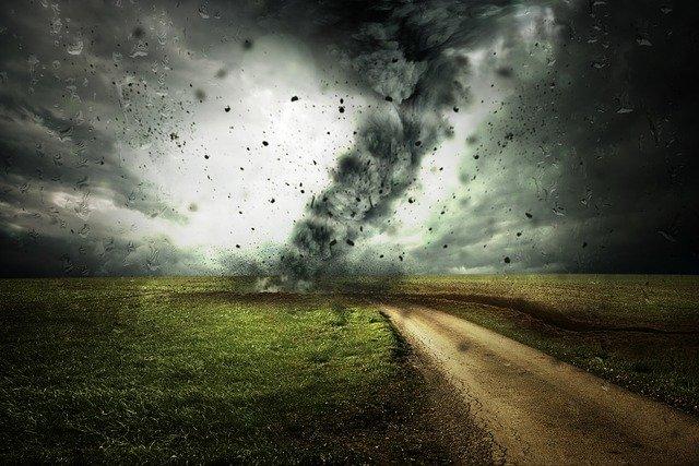 Twister tearing across an open field to a dirt lane, dark, moody sky