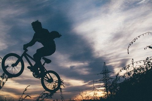 Young bike rider with wheels off ground, silhouetted against night sky