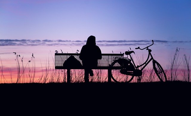 Silhouetted image of person sitting on a bench at sunset, bike beside bench