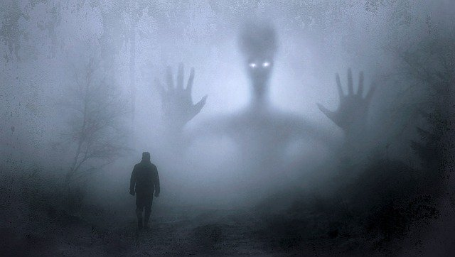 spooky monster hovering in background on foggy night, silhouette of man in foreground