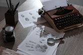 Typewriter, fingerprints and papers on desk in office. Detective's workplace